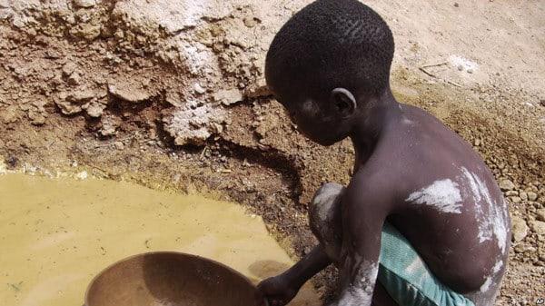 Abou Keita, 5 ans environ, cherche l'or à la mine de Djikouloumba, près de la région de Kankan, en Guinée, le 27 avril 2008.