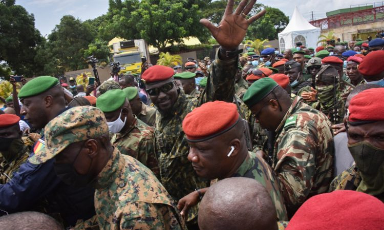 Lieutenant Colonel Mamady Doumbouya, head of the Army's special forces and coup leader, waves to the crowd as he arrives at the Palace of the People in Conakry on September 6, 2021, ahead of a meeting with the Ministers of the Ex-President of Guinea, Alpha Conde. - Lieutenant Colonel Mamady Doumbouya, the leader of the latest coup in Guinea, is a highly educated, combat-hardened soldier who once served in France's Foreign Legion. Doumbouya's special forces on September 5, 2021 seized Alpha Conde, the West African state's 83-year-old president, a former champion of democracy accused of taking the path of authoritarianism. (Photo by CELLOU BINANI / AFP)
